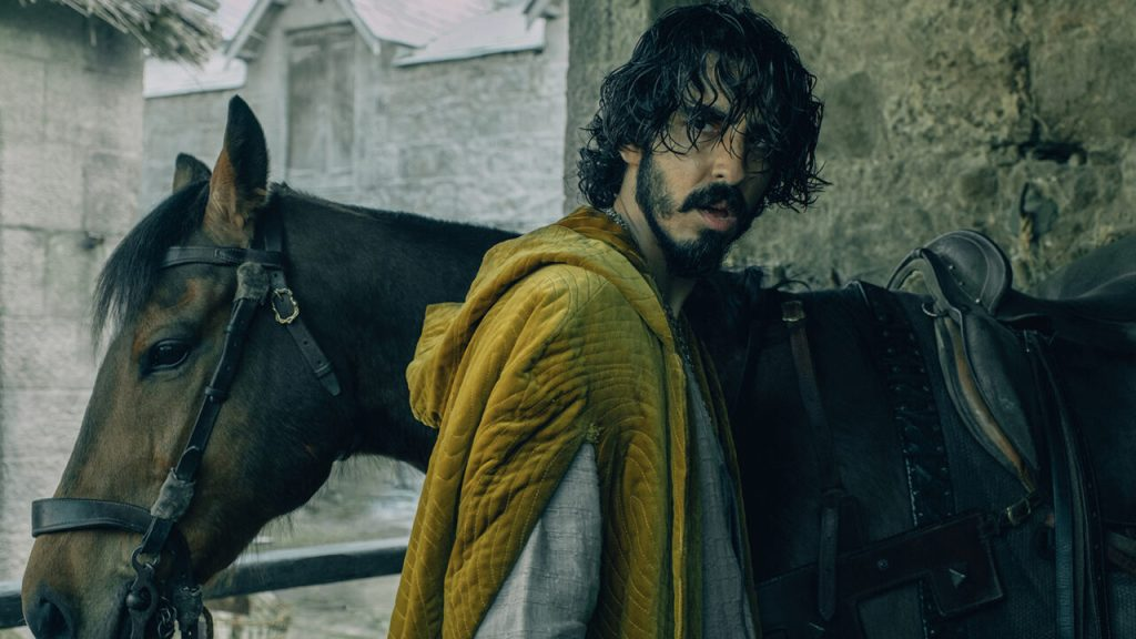 A dishevelled Gawain (Dev Patel) about to get on his horse.