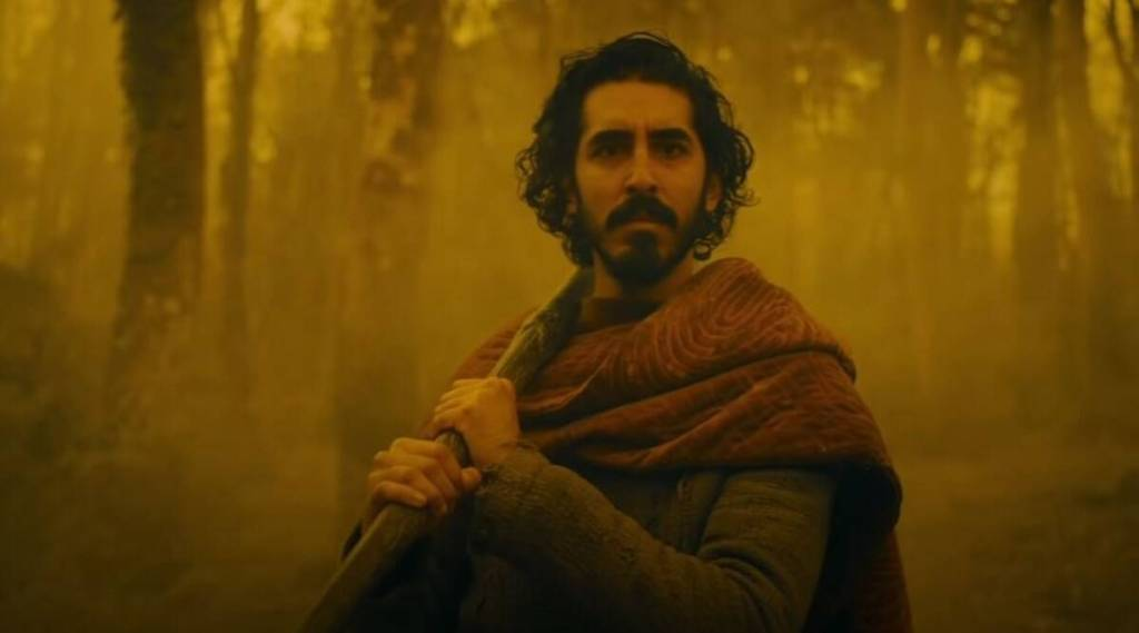 Gawain (Dev Patel) making his way through a foggy forest, everything bathed in yellow light.