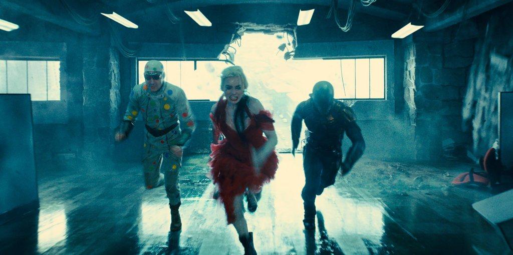 Polka-Dot Man (David Dastmalchian), Harley Quinn (Margot Robbie) and Bloodsport (Idris Elba) running in a building that is collapsing.
