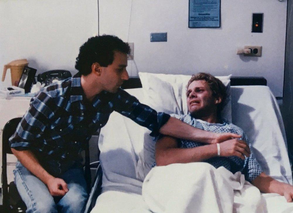 David (David Schachter) taking Robert's (Geoff Edholm) hand as he lies in the hospital bed.
