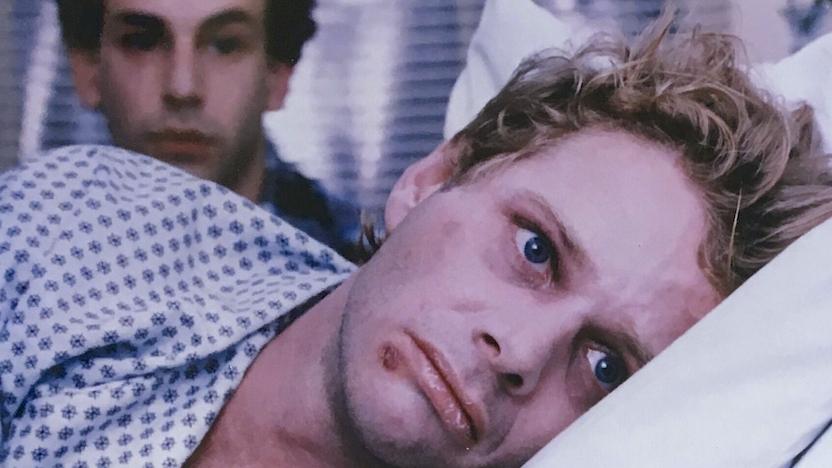 Robert (Geoff Edholm) lying in bed, facing away from David (David Schachtner).
