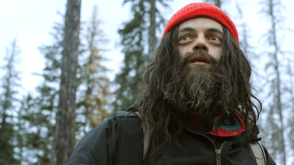 Buster (Rami Malek) with long hair and a long beard, both shaggy, in the forest.