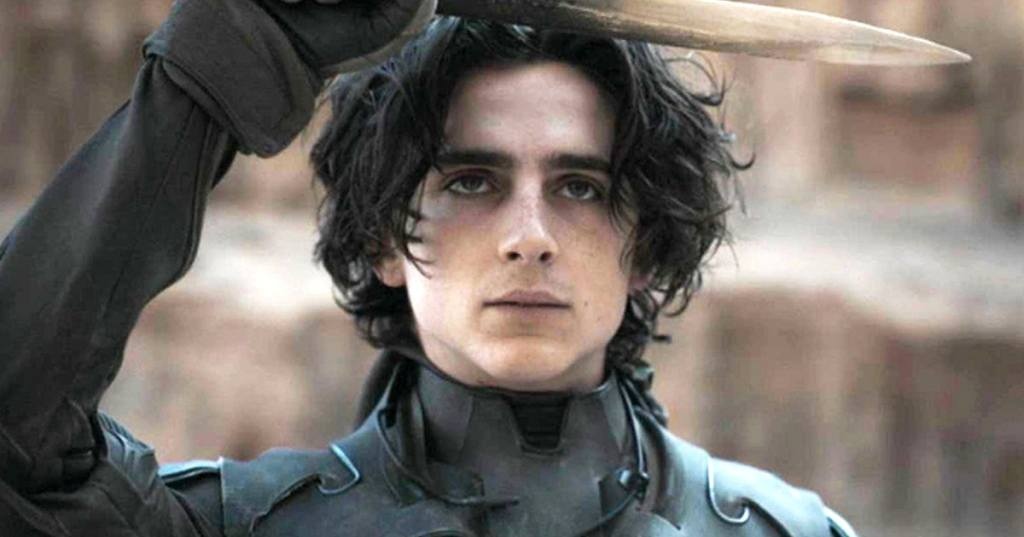 Paul (Timothée Chalamet) holding up a knife in a salute.