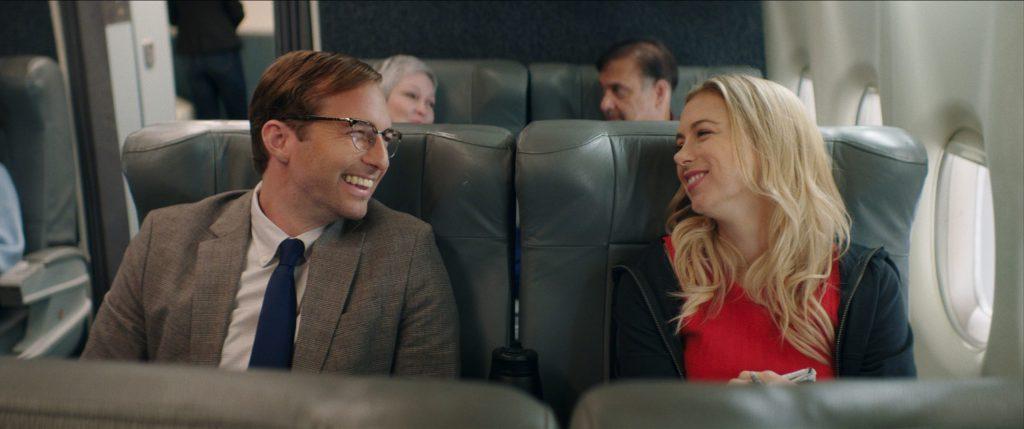 Andrea (Iliza Shlesinger) and Dennis (Ryan Hansen) talking on the plane.