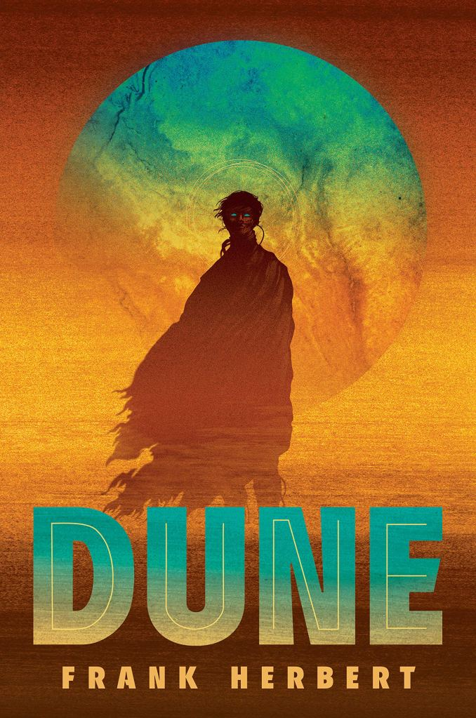The book cover showing a man wrapped in a cloak in front of an orange background. Behind him is a blue moon, his eyes also are a shining blue.