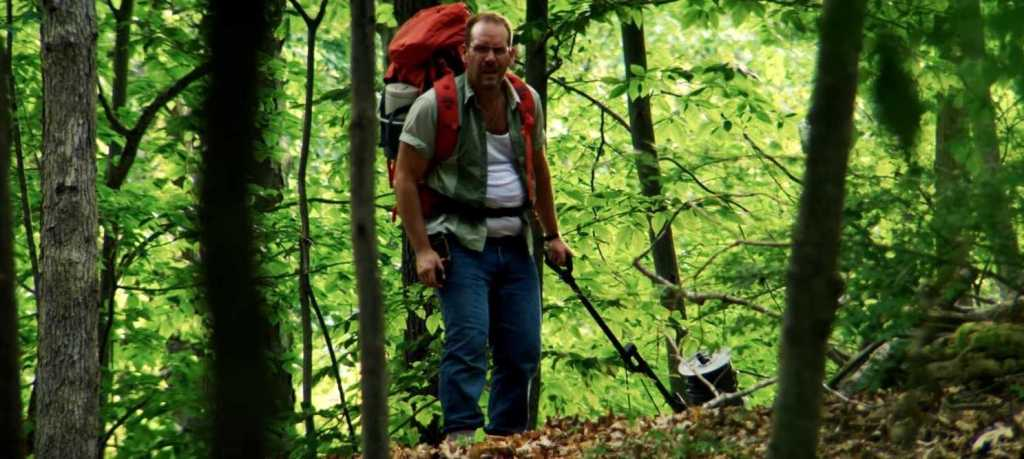 Ray (Dean Imperial) in hiking gear, pulling a cable through the forest.