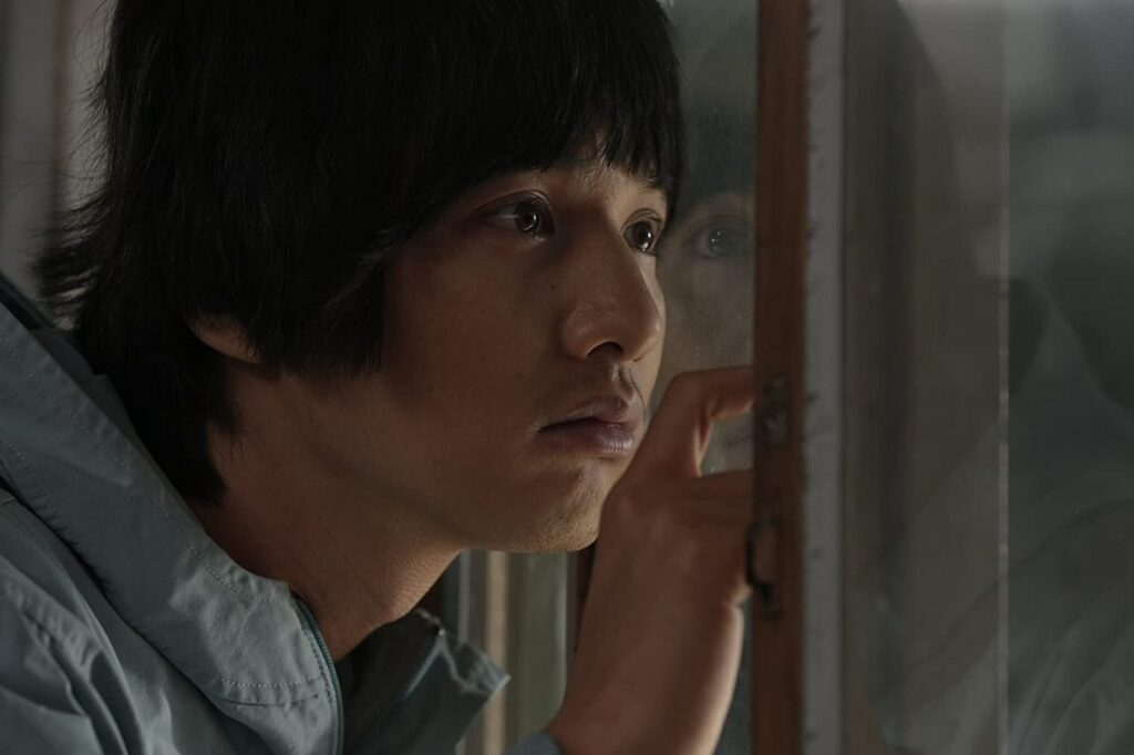 Yoon Do-joon (Won Bin) pressing his face against the partition in the prison visitor room.