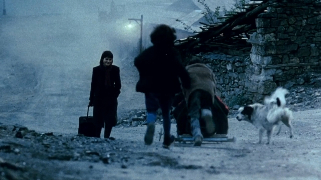 Lena (Anna Kapaleva) returning to her village, dragging a suitcase behind her.