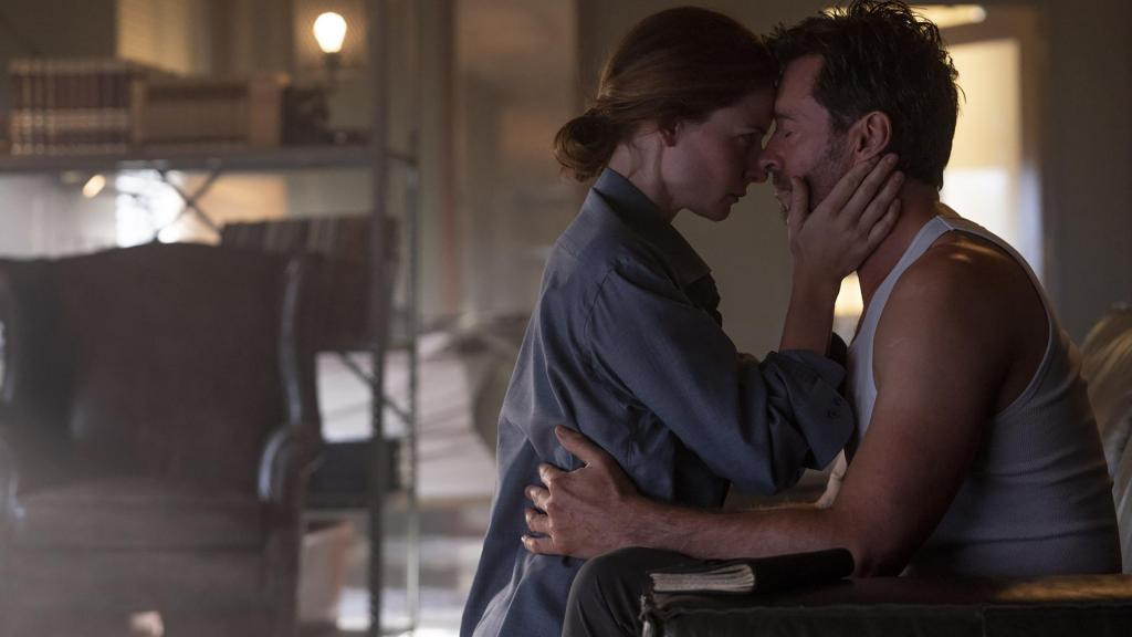 Nick (Hugh Jackman) and Mae (Rebecca Ferguson) kissing in his office.