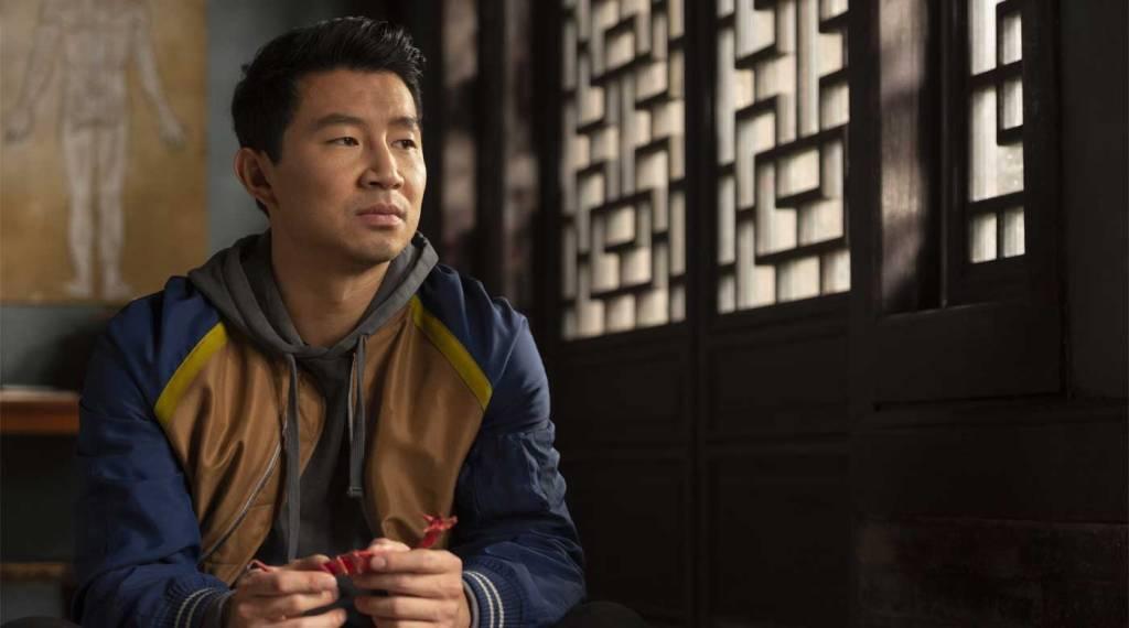 Shaun (Simu Liu) looking pensive, holding an origami dragon.