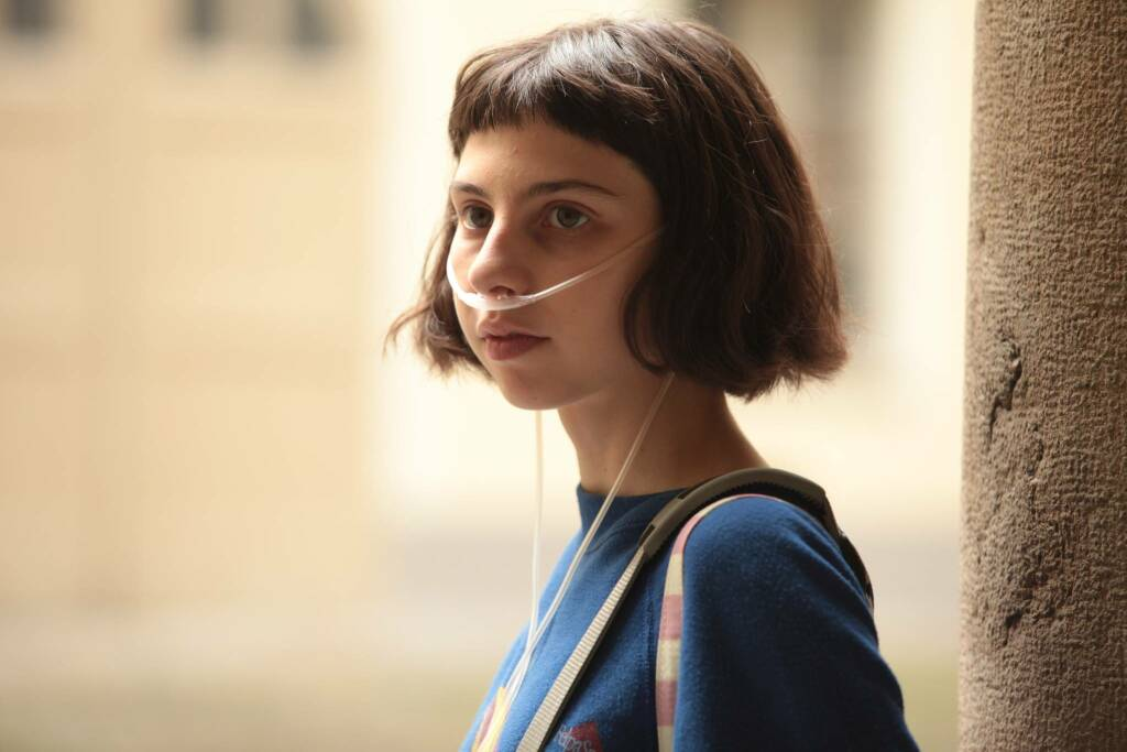 Marta (Ludovica Francesconi) with a breathing tube in her nose.