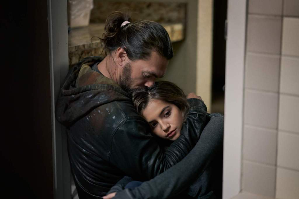 Ray (Jason Momoa) holding Rachel (Isabela Merced) tightly, kissing the top of her head.