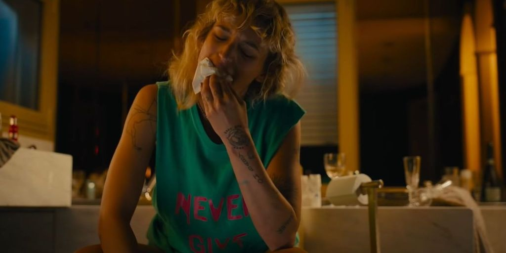 Alexia (Agathe Rousselle), kneeling on the bathroom floor, wiping her mouth with a tissue.