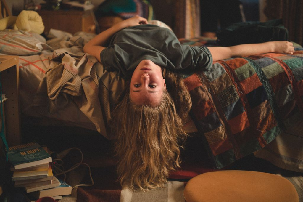 Mylia (Emilie Bierre) lying on her bed, her head dangling over the edge, upside down.