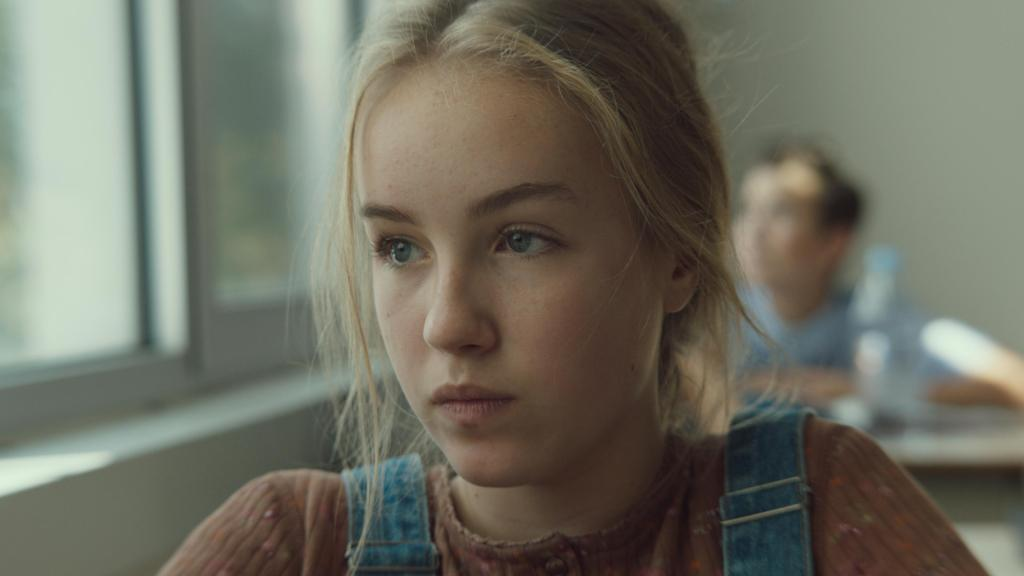 Mylia (Emilie Bierre) sitting in class, looking out the window.