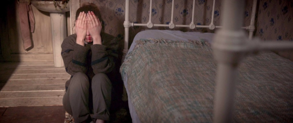 Olga (Leila Sykes) huddling next to her bed, hands in front of her eyes.