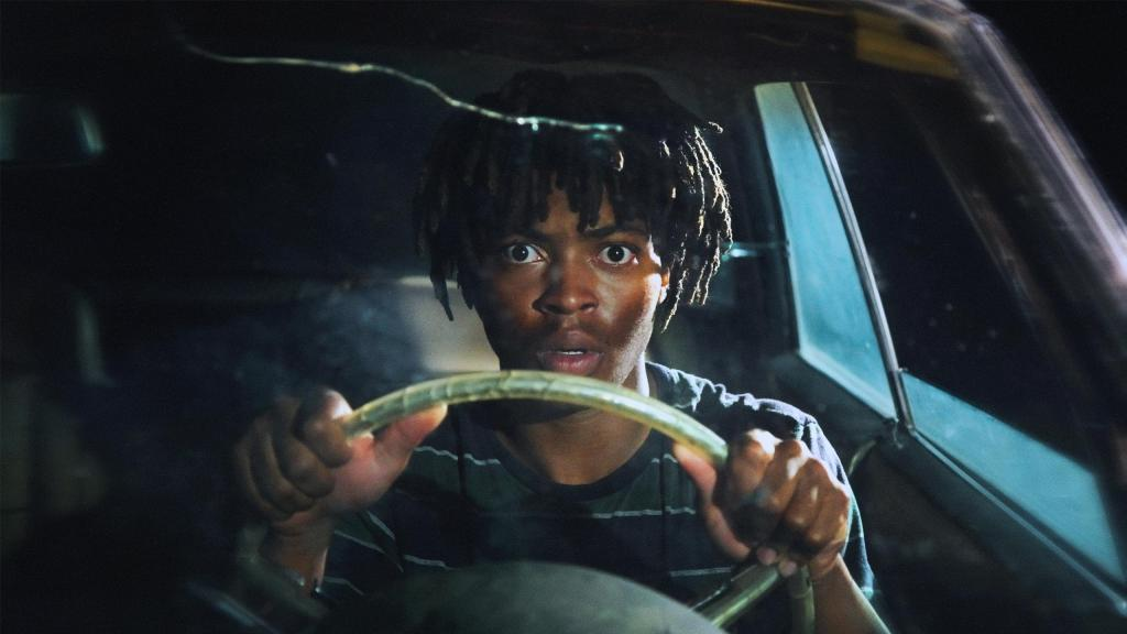 Mike (Tyson Brown) holding on tightly to the steering wheel of his car.
