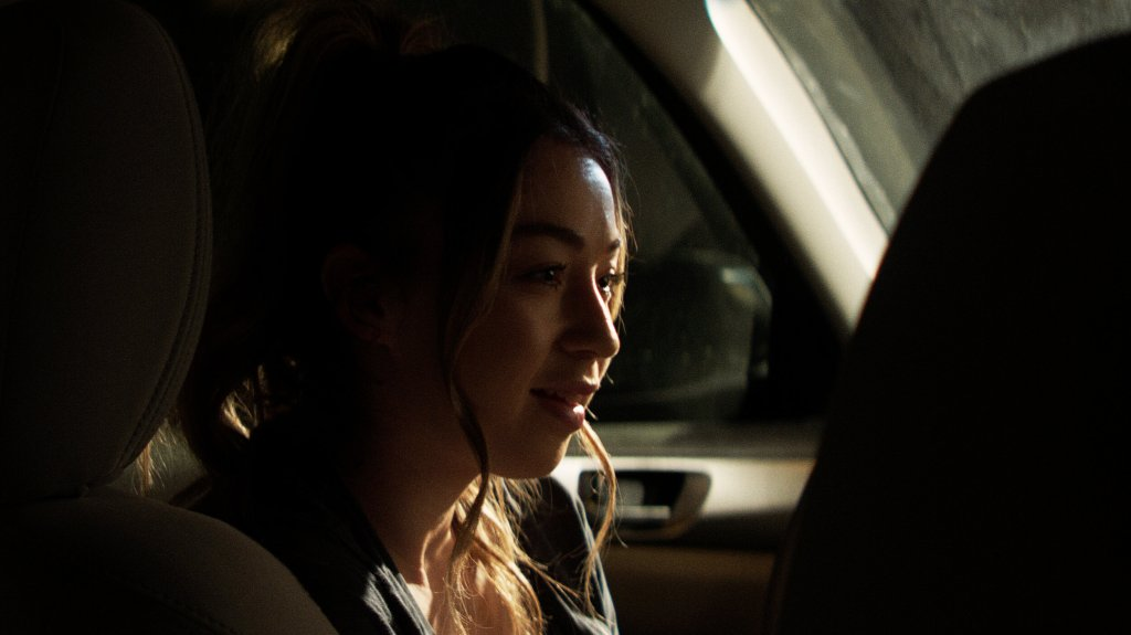 Kelsey (Shelby Duclos) sitting in the car, smilling.