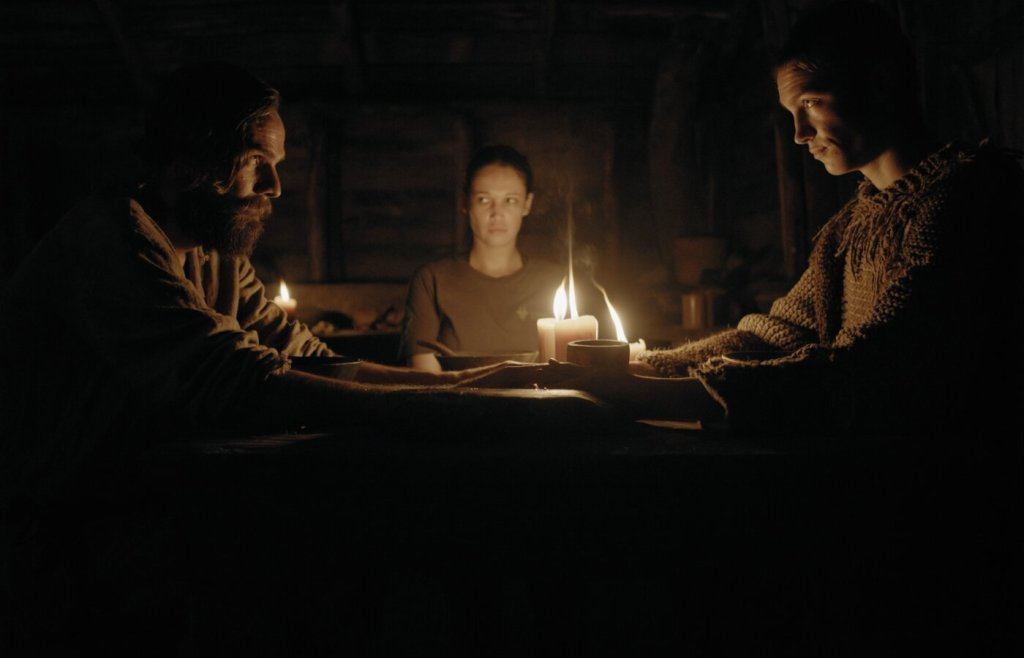 Gabi (Monique Rockman) sitting at a table with Barend (Carel Nel) and Stefan (Alex van Dyk), the latter two clasping hands as if in prayer.