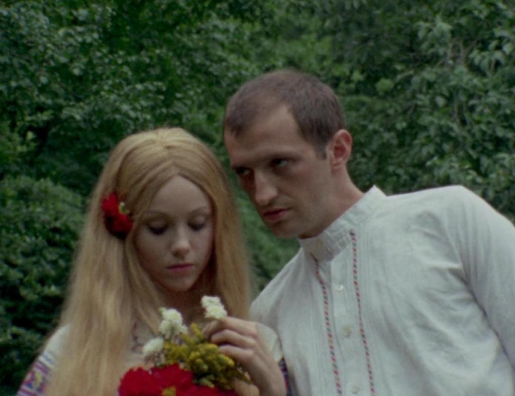 Radojka (Mirjana Nikolic) holding a bouquet of flowers and Strahinja (Petar Bozovic) leaning towards her.