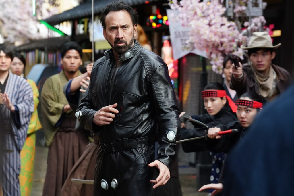 The hero (Nicolas Cage) in a fighting stance, surrounded by people who look about ready to attack.