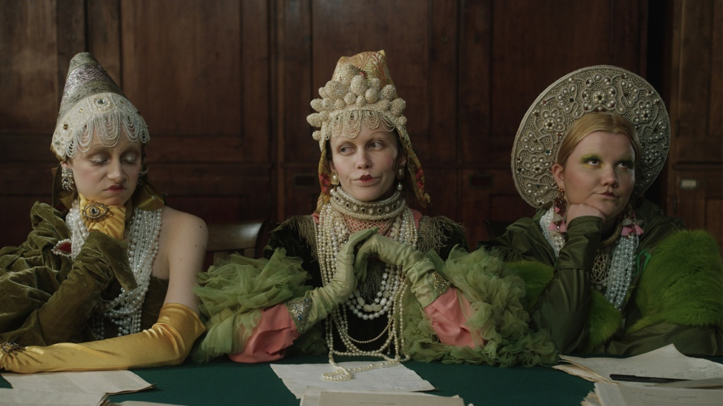 Three women in fancy headdresses and ballgowns sitting at a table looking very bored.