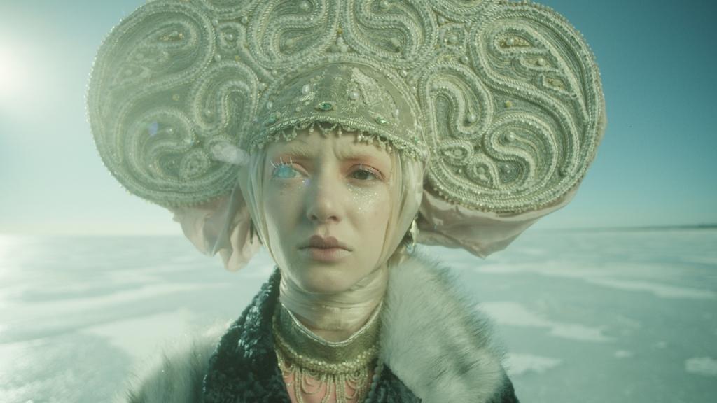 Polina (Alina Korol) standing in an icy landscape wearing a fancy headdress.